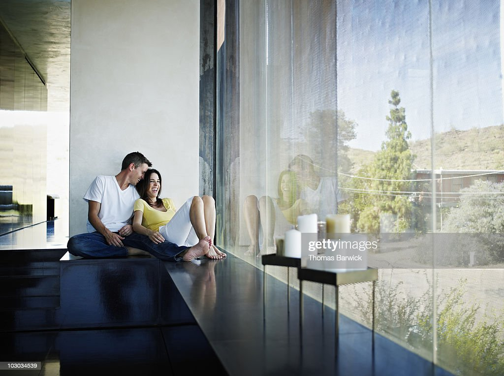 Husband and wife sitting near window of home : Stock Photo