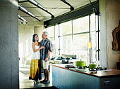 Husband and wife standing in contemporary home
