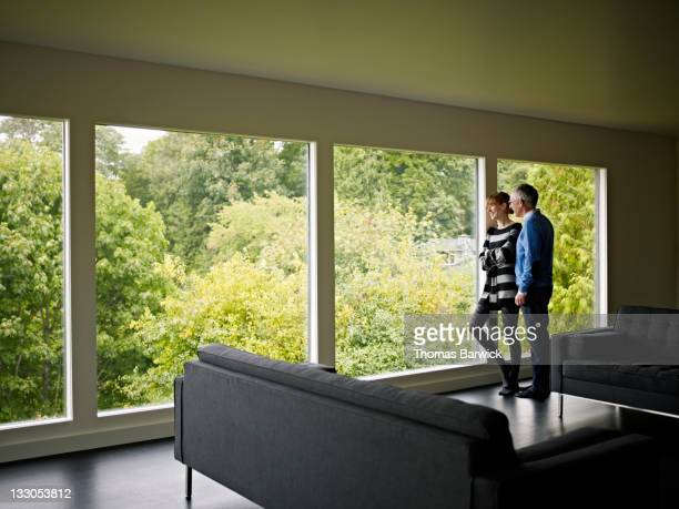 Husband and wife standing near window in home