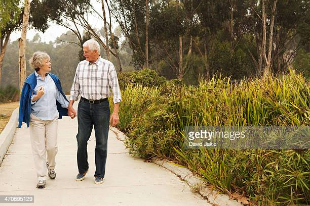 Husband and wife strolling and chatting in the park