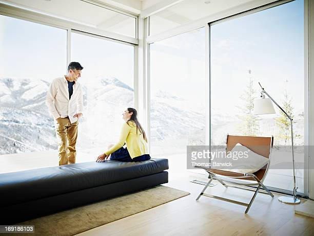 Husband and wife talking by windows with a view
