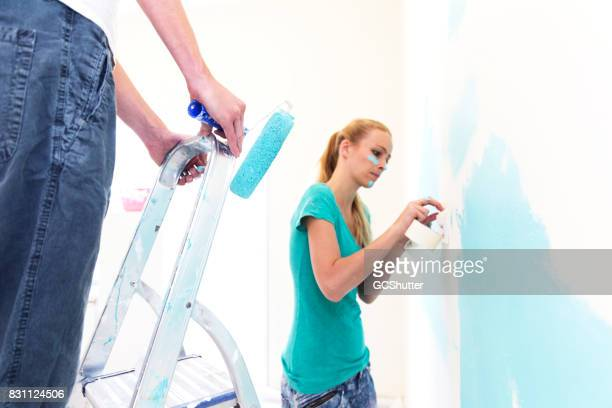 Husband and wife teaming up together to paint their new house blue.