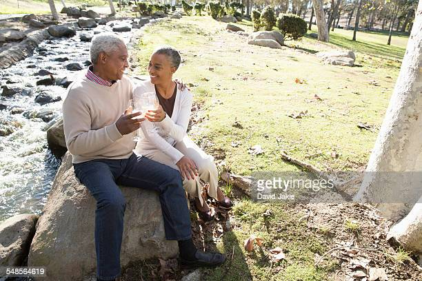 Husband and wife toasting by stream, Hahn Park, Los Angeles, California, USA