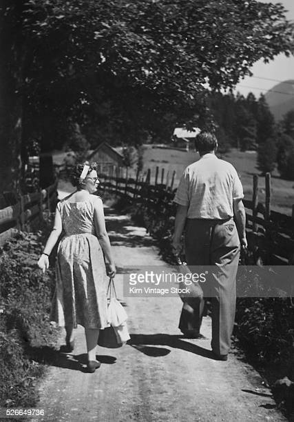 Husband and wife walk together on a rural path
