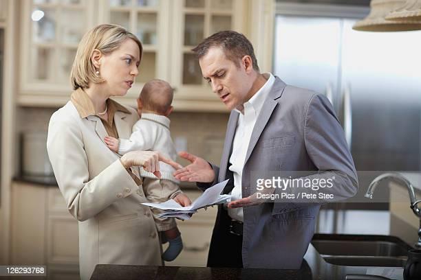 husband and wife with baby stressing over household bills