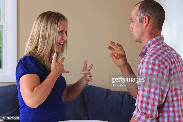 Husband and wife with hearing impairments signing excited in American sign language