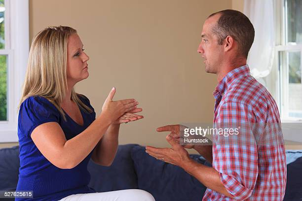 Husband and wife with hearing impairments signing Mortgage, Pay in American sign language