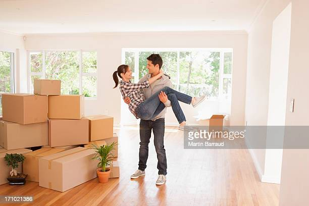 Husband carrying wife in new house