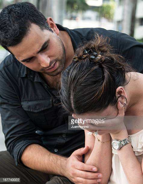 Husband consoles crying wife on a riverbank