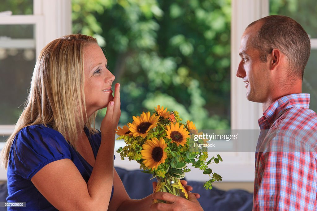 Husband giving flowers to his wife signing Thank You in American sign language both with hearing impairments