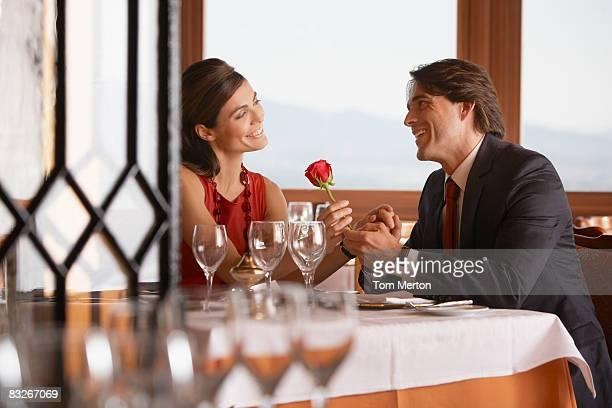 Mari donnant sa femme une rose dans un élégant restaurant