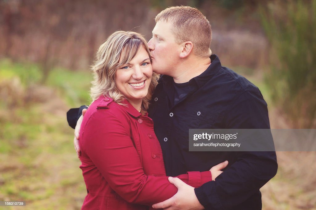 husband kissing wife in a field : Stock Photo