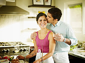 Husband kissing wife on cheek in home kitchen