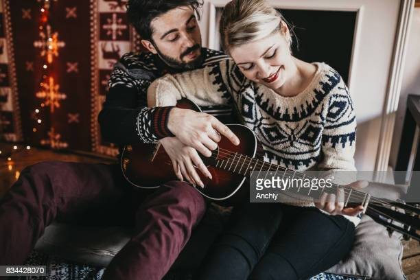 Husband learning his wife to paly guitar