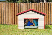 Husband or boyfriend man sleeping in the doghouse because of domestic problems with his wife or girlfriend like fighting, cheating infidelity, too much partying with the boys, won't help with chores.