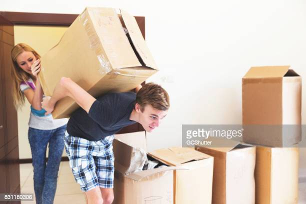 Husband piggy-backing a large heavy carton on his back while his wife tries to balance the rear end