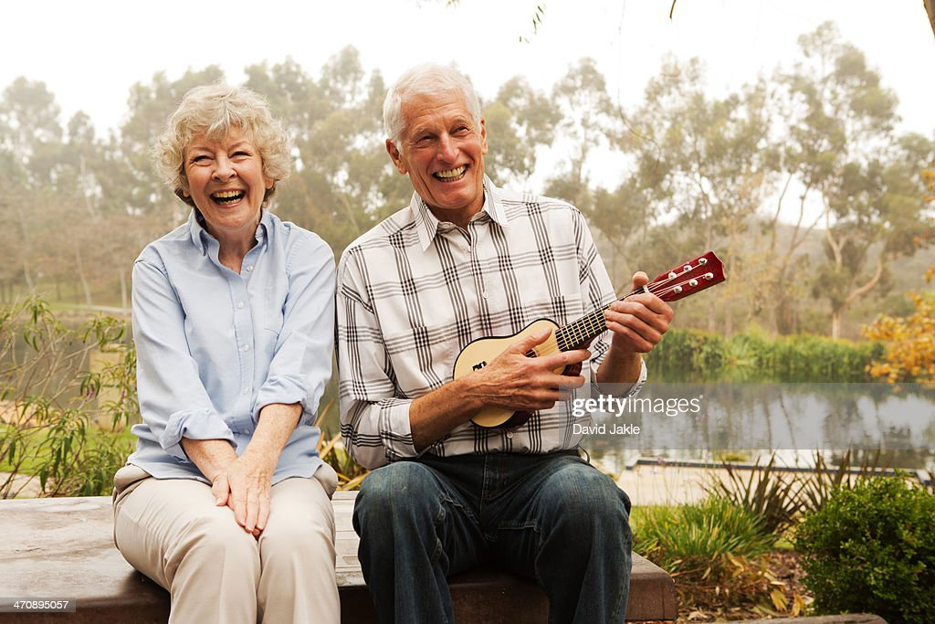 Husband playing the ukulele with wife by lake