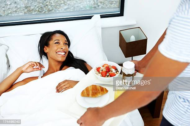 Husband serving breakfast for wife in bed