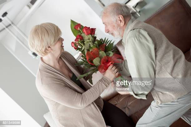 Husband surprises his wife with bouquet of red roses