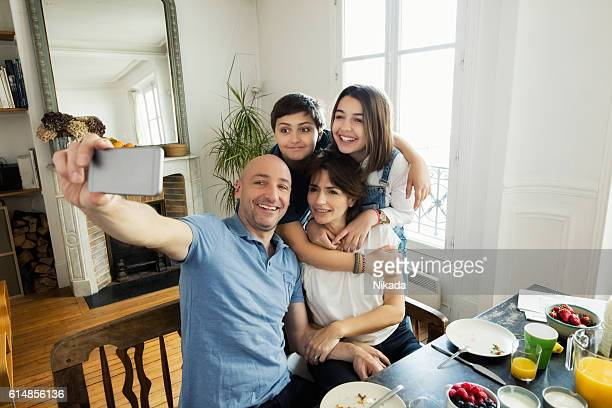 Husband taking selfie with wife and children at breakfast table