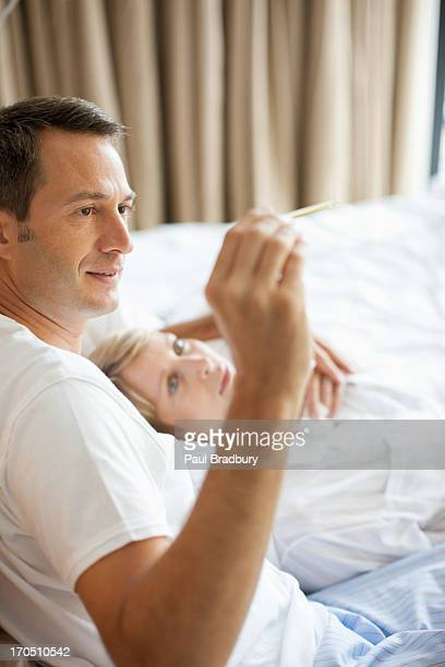 Husband taking wife's temperature