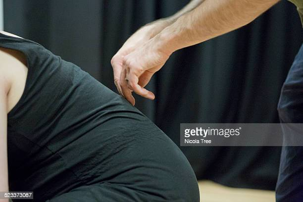 Husband trying massage technique at antinatal clas