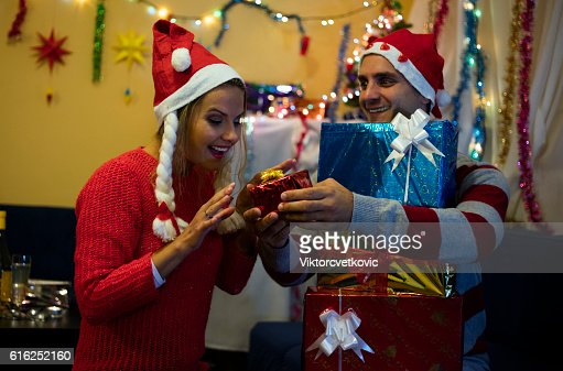 Husband with gifts surprised his happy wife. Happy New Year. : Foto de stock