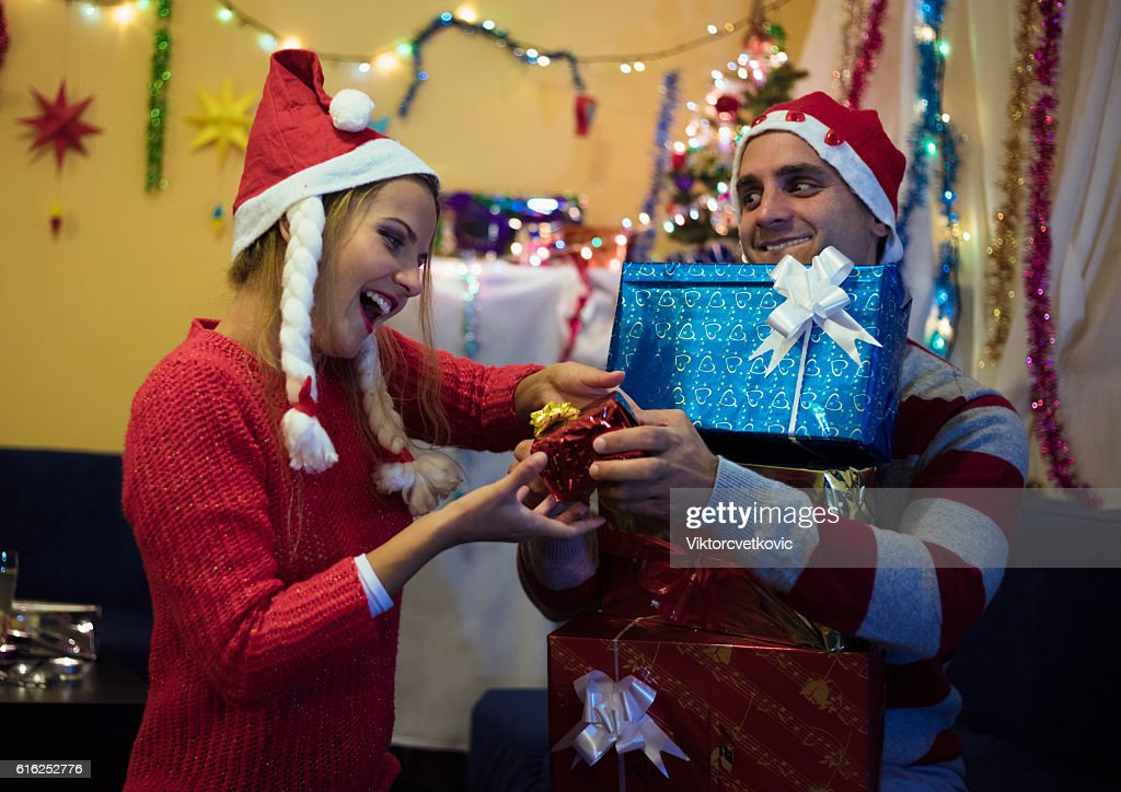 Husband with gifts surprised his happy wife. Happy New Year. : Stock-Foto