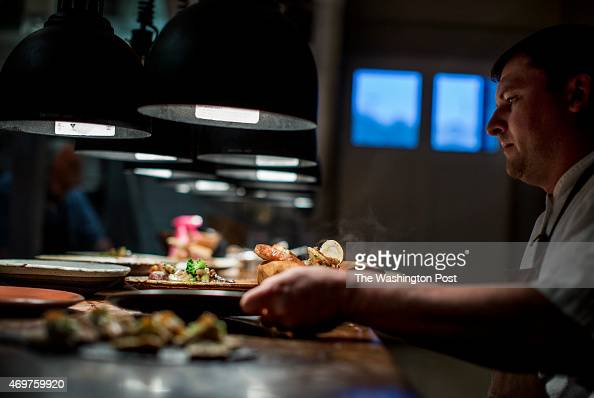 Husk's Chef Sean Brock inspects and passes off the finished dishes to servers from the Husk kitchen in Charleston South Carolina on Friday March 13...