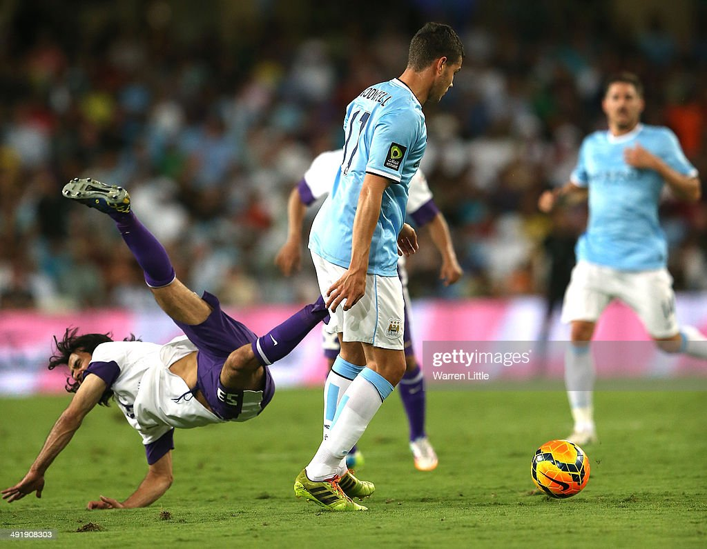 Hussain Abdulghani of Al Ain is knocked off his feet in a tackled with Jack Rodwell of Manchester City during the friendly match between Al Ain and Manchester City at Hazza bin Zayed Stadium on May 15, 2014 in Al Ain, United Arab Emirates.