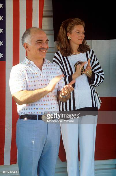 Hussein bin Talal and his wife Noor sovereigns of Jordan side by side in casual civil clothes clap fun during an informal diplomatic meeting on the...