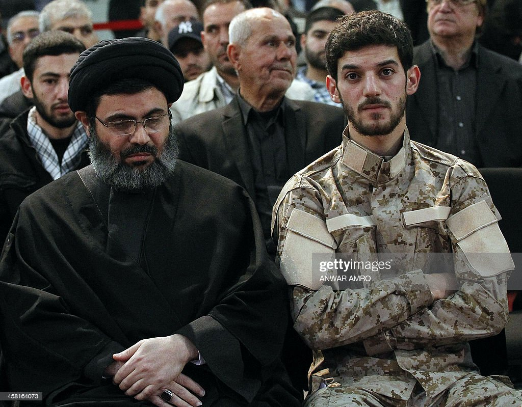 Hussein Lakkis (R), the son of Hassan Hawlo al-Lakiss a top member of the Shiite Hezbollah movement who was murdered on December 4, and Hashim Safieddin (L), the head of Hezbollah's political bureau watch a televised speech by the movement's chief Hassan Nasrallah in Beirut on December 20, 2013. Nasrallah warned that his Lebanese Shiite movement will 'punish' Israel for the killing of a top leader earlier this month.
