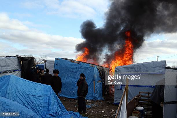 A hut burns as part of the 'jungle' migrant camp is cleared on February 29 2016 in Calais France The French authorities have begun dismantling part...