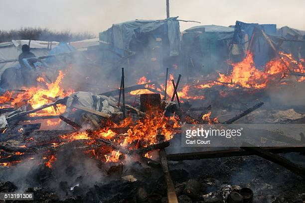 A hut burns as police and demolition workers clear the 'jungle' migrant camp on March 01 2016 in Calais France Police and demolition teams are...