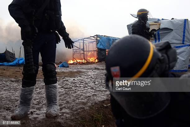 A hut burns behind police officers as police and demolition workers clear the 'jungle' migrant camp on March 01 2016 in Calais France Police and...