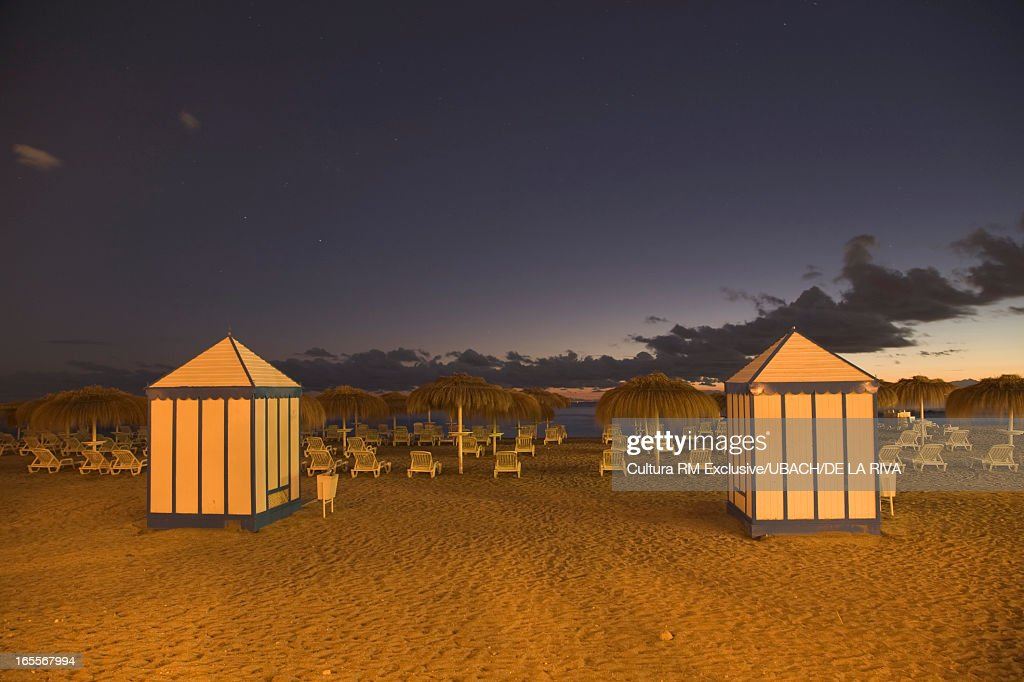 Huts and lawn chairs on tropical beach : Stock Photo