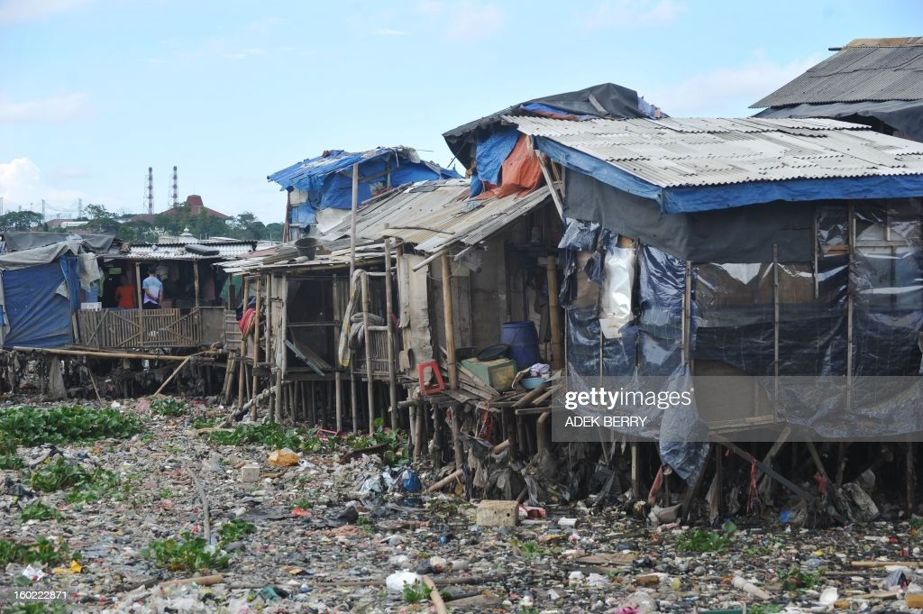 Huts stand on the Pluit dam that is full of garbages in Jakarta on January 28, 2013.