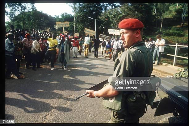 Hutus celebrate the arrival of French troops at the Zaire border while a soldier stands guard June 24 1994 in Rwanda The Hutus believe that the...