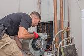 Hvac repair technician removing a blower motor from air handler