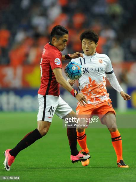 Hwang Ilsu of Jeju United FC and Rota Moriwaki of Urawa Red Diamonds compete for the ball during the AFC Champions League Round of 16 match between...