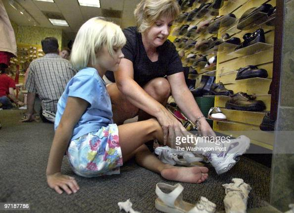 hxshop 081804 Columbia Md Mark Gail/TWP Patricia Eakin keeps her daughter Natalie busy by seeing what different shoes will look like on her while...