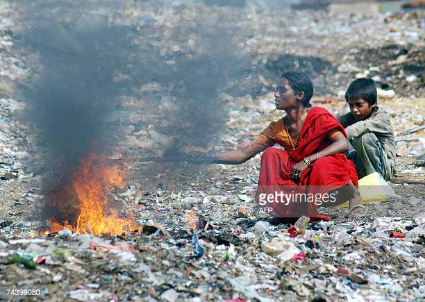 An Indian mother and her son burn waste in order to retrieve the copper wire at the garbage dump in the Borabanda slum in Hyderabad 05 June 2007 on...