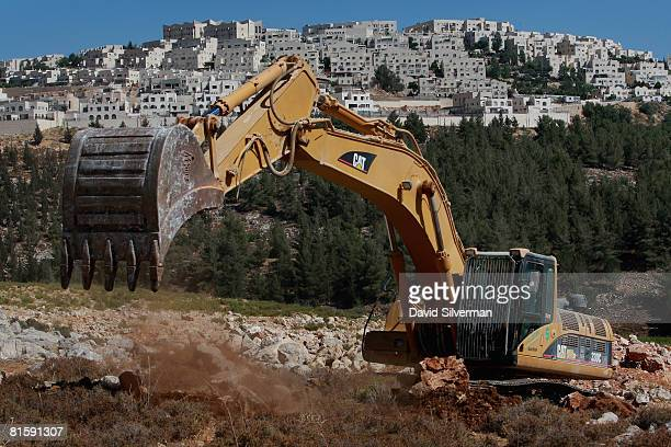 A hydraulic excavator breaks ground for a new section of Israel's separation barrier near the Jewish neighborhood of Ramat Shlomo on June 16 2008...