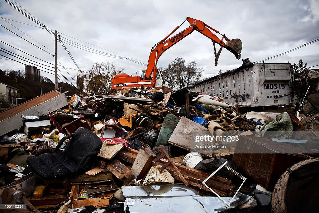 A hydraulic excavator dumps trash, aggregated into a central location after Superstorm Sandy destroyed numerous homes on November 1, 2012 in Highlands, New Jersey. Superstorm Sandy, which has left millions without power or water, continues to affect business and daily life throughout much of the eastern seaboard.