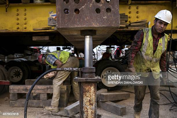 A hydraulic jack is seen holding a support beam as workers remove dollies and replace them with rollers for the final stages of moving a historic...