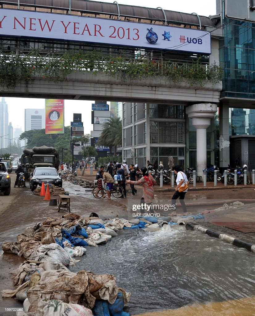 Hydro pumps remove water after flooding inside a building's parking lot in downtown Jakarta on January 19, 2013 after three bodies were pulled out of the floodwaters