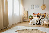 Candles on wood next to bed with knit blanket in hygge style bedroom interior with brown curtain and posters