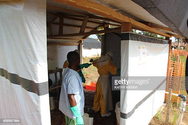 Hygienists get disinfected after cleaning a part of the Ebola treatment centre in Lokolia on October 5 2014 AFP PHOTO KATHY KATAYI