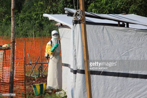 Hygienists wearing protective suits disinfect the toilets of the Ebola treatment centre in Lokolia on October 5 2014 AFP PHOTO KATHY KATAYI