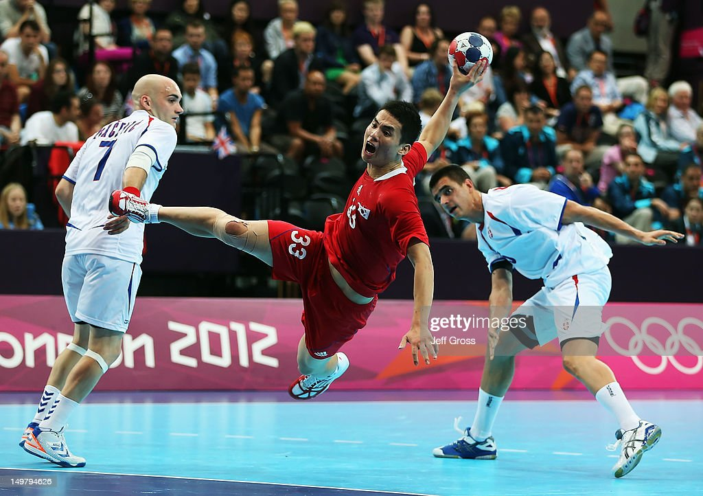 Hyowon Eom #33 of Korea shoots between Ivan Nikcevic (L) #7 and <a gi-track='captionPersonalityLinkClicked' href=/galleries/search?phrase=Zarko+Sesum&family=editorial&specificpeople=5668700 ng-click='$event.stopPropagation()'>Zarko Sesum</a> (R) #5 of Serbia during the Men's Preliminaries Group B match between Korea and Serbia on Day 8 of the London 2012 Olympic Games at the Copper Box on August 4, 2012 in London, England.